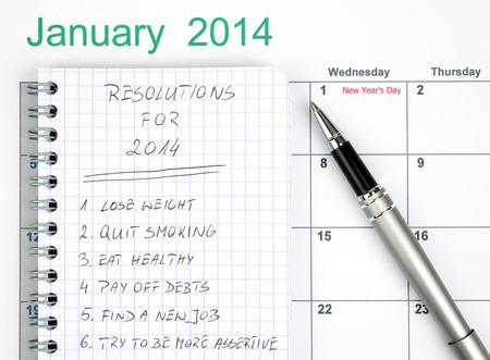 New Years resolutions listed in the notepad with calendar and pen