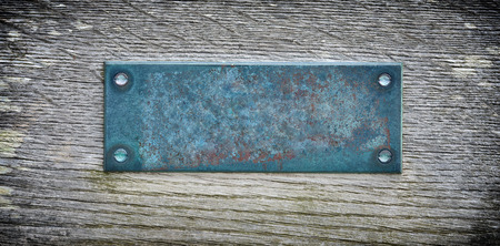 Aged metal plate on wooden background