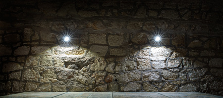stonemason: Stone wall and a table lighted two lamps Stock Photo