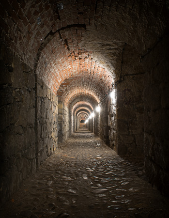 vanish: Old medieval brick tunnel with light at the end Stock Photo