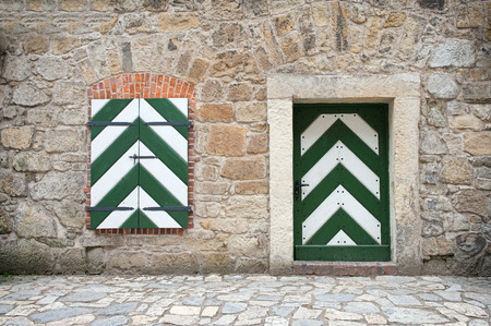 locked door: Old stone wall with wooden door and window painted in white and green. Stock Photo