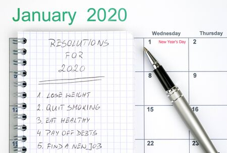 New Year resolutions listed in the notepad with calendar and pen