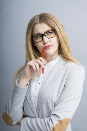 business backgound: Young thoughtful business woman in an official suit and glasses holding pencil standing on the gray backgound Stock Photo