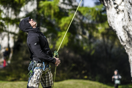 Man belaying a rope during climbing his partner, Jura krakowsko czestochowska. Editorial