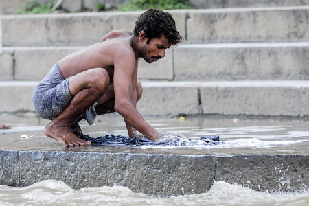 benares: Varanasi, India, september 19, 2010: Indian man making laundry in ganges river in Varanasi.