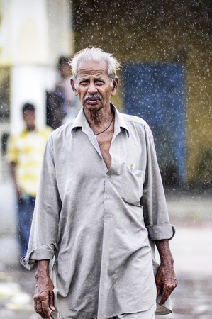 Udaipur, India, september 13, 2010: Indian old man walking in rain on Udaipur streets. Editorial