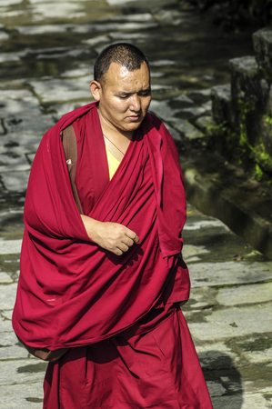 Dharamsala, India, september 6, 2010: Tibetan monk walking in traditional wearing.