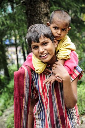 Dharamsala, India, september 6, 2010: Indian siblings smiling on a street od Dharamsala.