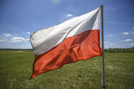 Polish flag waving on a wind, summer time, sunny day. Stock Photo