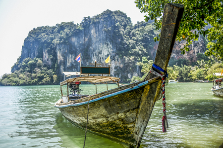 Boat on a Railey beach in Krabi, Thailand, with a cliff in background. Stock Photo