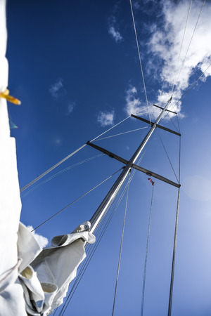 Mast in cloudy sunny day, with sails, summer time. Stock Photo