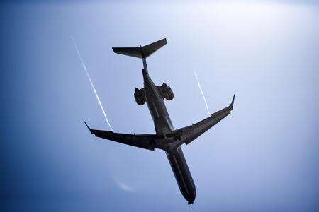 View of an airplane flying over the sky, view from below.