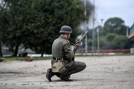 Gryfino, Poland, 23 september 2017: Historical reconstruction of the battle at Arnhem, a German soldier aiming with a rifle.