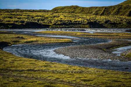Icelandic landscape, lava fields covered with moss and stream in the foreground