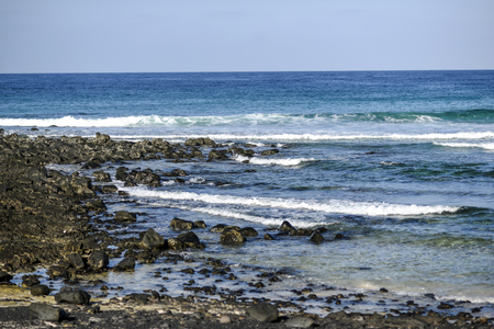 Volcanic rocks protruding from the assessment at the coast of the island of Lanzarote