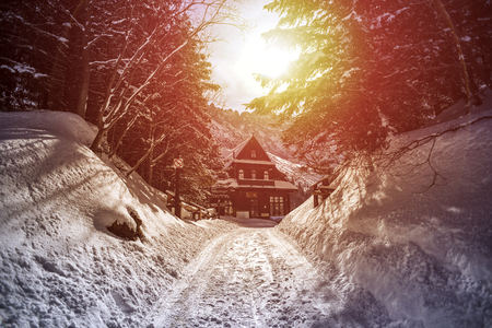 Winter mountain landscape in vintage style. Morskie Oko hostel in the Polish Tatra mountains in winter. Фото со стока