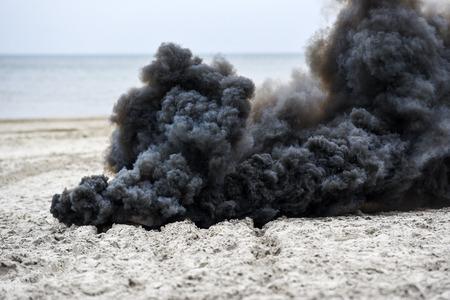 Explosion on the beach, billowing black smoke.