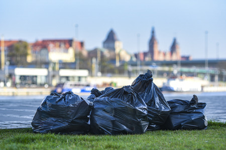 Garbage in black sacks against the background of the city. Banco de Imagens
