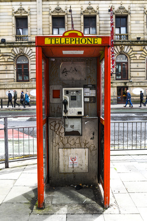 Dirty red telephone box in the city center in England. Banco de Imagens