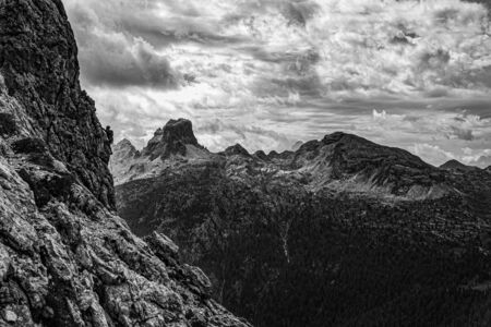 Monochrome picture of climber on the rock in the Dolomites against the backdrop of the mountains panorama. Banco de Imagens - 130806226
