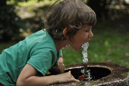 gaping: Little boy drinking water from the tap in the park.