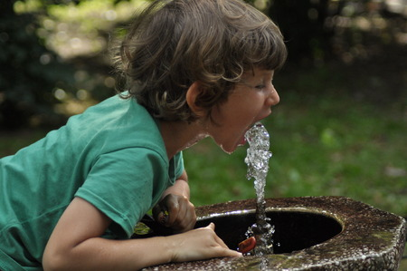 water park: Little boy drinking water from the tap in the park.