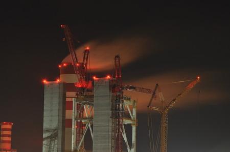 smokestacks: Power plant. Crane at a construction site. Chimney and smoke