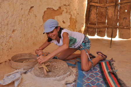 berber: The girl grinding flour in the mill. Tourism in ezgotycznych countries. Round trip. Berber culture. Stock Photo