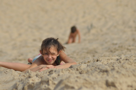 Boy and girl siblings in the dunes. The sand in the desert in the Slowinski National Park, Tourism
