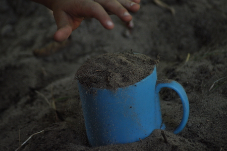 childs: Sand, mug, childs play in the sand. Hands of the child.