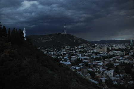 dark city: Tbilisi. View of the city and a monument to the mother of Georgia from the hill during the storm. Stock Photo