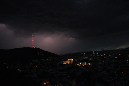 prowess: Tbilisi. View of the city and a monument to the mother of Georgia from the hill during the storm. Stock Photo
