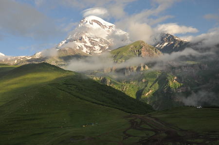 siete: Snow-capped mountains Kazbek at dawn and the valley below where there is a church siete Trinity. Georgia.