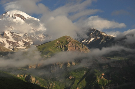 Snow-capped mountains Kazbek at dawn and the valley below where there is a church siete Trinity. Georgia.
