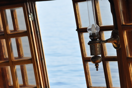 Sea view through the open window. Kerosene lamps on the ship. Stock Photo