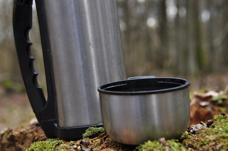 to maintain: Hot tea in thermos for a walk in the woods while resting Stock Photo