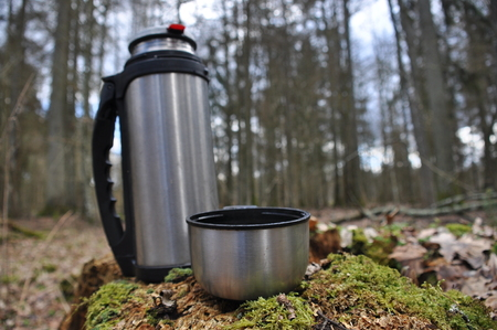 to maintain: Hot tea in flask for a walk in the woods while resting Stock Photo