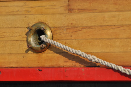 durable: A mooring rope coming out of the hole in the side of the ship. Thick twisted rope. Stock Photo