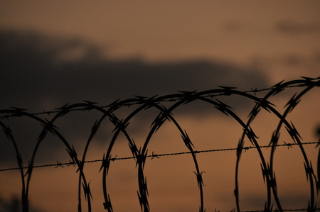 Fence with barbed wire. Barrier, entry ban Stock Photo