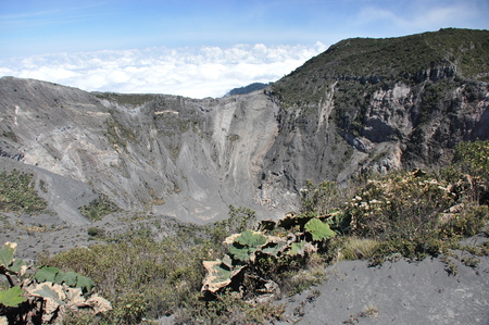 Irazu volcano in Costa Rica. Crater in clouds with protective barriers. Fragments of lava and pumice.