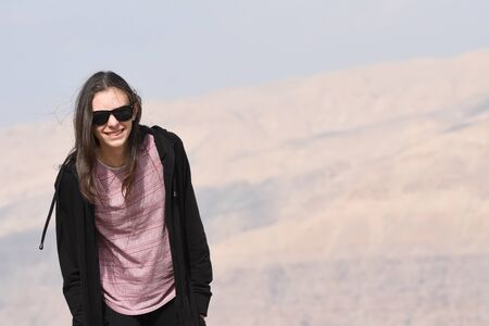 A young girl in a black sweatshirt and sunglasses on the background of rocks on the mountainside near the fortress of Al Karak in Jordan.