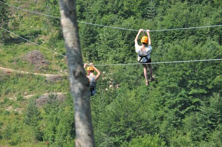 Mother and daughter riding down a zipline over the Tara Gorge, a river in Montenegro with the deepest canyon in Europe. Girls in harnesses with helmets on their heads.