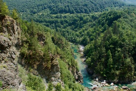 The bridge on the Tara River in Montenegro and the bridge connecting the two banks of the canyon. A stony bed of a clean river flowing through the valley along the road on a mountain slope. Standard-Bild