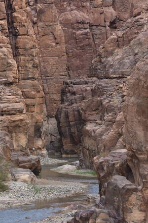 Entrance to the Wadi Mujib canyon in Jordan. Steep rocks and a rapid flowing river carved. Difficult crossing and attraction for tourists on the water route. 写真素材