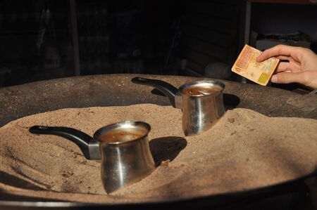 Arabic coffee brewed in a brass metal crucible in hot sand on one of the street stalls in Aqaba, Jordan. Aroma of coffee with cardamom and sugar for 1 Jordanian dinar.