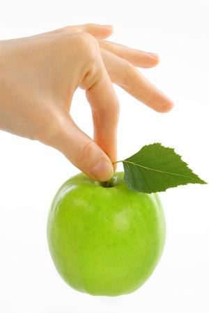 woman, female hand take green apple with leaf photo