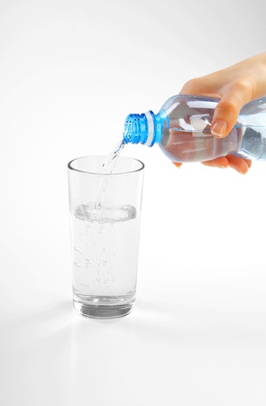 woman hands pouring fresh blue water from bottle Stock Photo