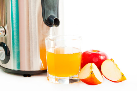 Juice extractor and freshly squeezed apple juice isolated on white photo