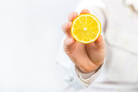 手は、白で隔離されるレモンを保持する女性