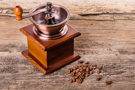 coffee beans and old coffee mill in shop, cafe on wooden table photo